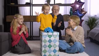 Cute little toddler boy unwrapping his birthday present from grandparents indoors. Sweet family clapping hands while grandson jumping from happiness, opening gift box and taking out his present