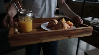 Delicious breakfast on wooden tray served by man
