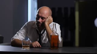 Depressed hopeless middle aged bearded businessman leaning on glass of whiskey while drinking alcohol beverage alone in domestic room at night. Man escaping reality and problems in alcohol abuse.