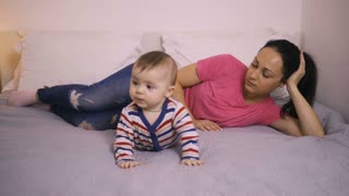 Depressed young mixed race mother lying on bed with her baby son and staring away with upset look. Tired, sad and exhausted mother unhappy near her cheerful infant child