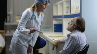Doctor examining man's throat with tongue depressor