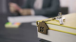 Dolly shot of property keys with wooden house keychain on the pile of notebooks with blurry female real-estate agent in formal suit working on the background. Real estate, house ownership concept
