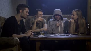 Drug addicted youth using cocaine at the table in a gloomy domestic room on the couch. Young people drinking, smoking and talking, while man in a hoodie uses rolled-up dollar bill to sniff cocaine