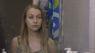 Drug paraphernalia. Young blond woman addicted to drugs using breathe spray near the mirror in the bathroom at home to cover up drug use. Drug abuse, addiction, social issues concept