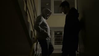 Drug pusher making drug sale to young addict customer in a dark building with stairway at night. Addict and dealer exchanging cash and cocaine on the staircase. Drug abuse, addiction, social issues