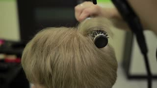 Drying female customer's hair with dryer and brush