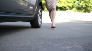Elegant female legs in red heels getting into car