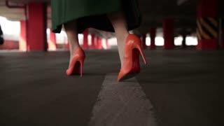 Elegant female legs walking to parked car