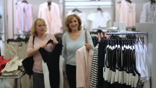 Elegant women looking for dress in clothing store