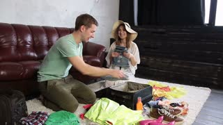 Excited couple packing traveler case for vacation