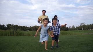 Excited laughing and smiling adorable asian little siblings holding hands running on green park lawn with happy multi ethnic parents following them while family enjoying weekend in park. Slow motion.