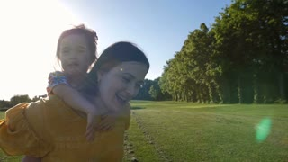 Excited little toddler girl with down syndrome riding on mother's back while mom is running on green meadow in summer. Happy girl and mom laughing and enjoying together during sunset in nature