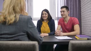 Excited young adults couple sitting at the table with female real-estate agent. Female realtor offering happy family their new home keys. Attractive young people taking the keys, smiling and kissing