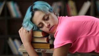 Exhausted female student napping on pile of books