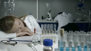 Exhausted scientists sleeping on workplace in lab