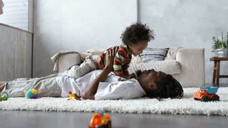 Father bonding with toddler son lying on carpet