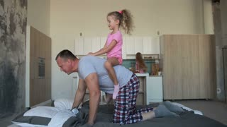 Father giving piggyback ride to daughter at home