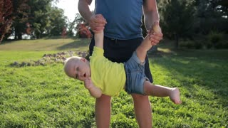 Father swinging toddler son upside down in park