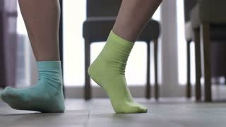 Female feet in dancing indoors in socks of different color. Woman making funny funky dance moves with legs and feet in mismatched socks at home.