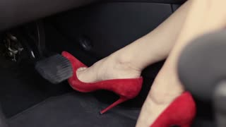 Female foot in high heels pushing car brake pedal