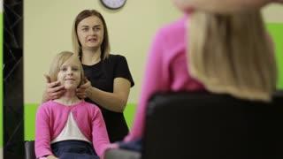 Female hairdresser asking girl how to cut hair in salon