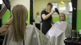 Female hairdresser drying hair with blow dryer