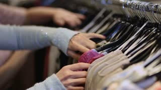 Female hands selecting colorful clothes on hangers