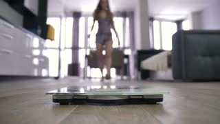 Female with measuring tape in hands approaching and her feet standing on body weight scales to measure weight. Happy woman jumps of the scale and starts dancing, celebrating weigh loss.