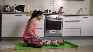 Fit female doing downward-facing dog yoga pose and kissing her baby son, lying on yoga mat in the kitchen at home. Attractive mother stretching together with her cute infant child. Dolly shot