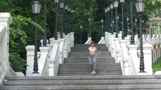 Fit mature redhead woman doing cardio in the morning. Beautiful slim athletic female running down the stairs in park. Healthy lady taking steps down. Healthy lifestyle and sport concept