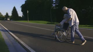 Fit senior husband pushing and spinning his disabled wife on wheelchair during a walk in summer park. Happy cheerful aged couple with gray hair having fun during leisure in park. Steadicam