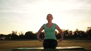 Fitness woman exercising yoga poses at sunset