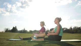Fitness women doing pilates leg stretches exercise