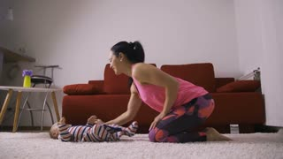 Fitness young mother making push-up excercise s her baby boy lies on excercise mat. Sporty female kissing infant child during workout in living room. Mother and baby having fun together at home. Dolly