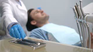 Foreground dental instruments. Background blurry young male patient in dental chair and female dentist in lab coat and gloves. Doctor's hands taking dental tools and start examining patient's teeth