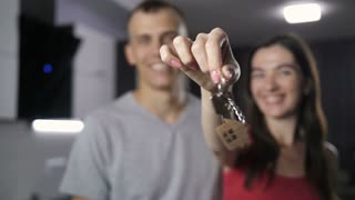 Foreground key chain with new house keys and wooden house shaped key ring, background happy smiling young couple moving to the house of their dreams