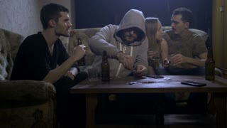 Four young alcoholics sitting on sofa at night in domestic room at home, abusing alcohol while hooded shirt male rolling marijuana joint. Alcohol abuse, social issues and drug addiction concept