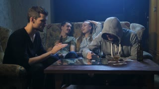 Four young drug addict friends sitting on the couch ready to use cocaine indoors at night. Men and one woman relaxing, laughing, drinking alcohol, as their friend makes cocaine line using credit card.