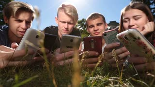 Friends in circle using smartphones on park lawn