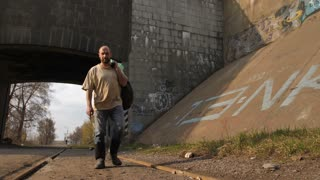 Front view full length of mature bearded homeless man in dirty clothes walking near bridge tunnel in city. Male in boots holding plastic bin bags with trash and belongings. Steadicam stabilized shot.