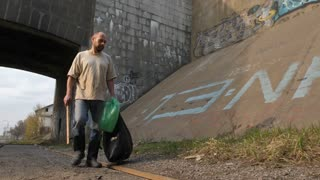 Front view full length of mature bearded unemployed man walking in city near bridge, collecting empty plastic bottle from the ground, and putting it into bin bag. Steadicam stabilized shot.
