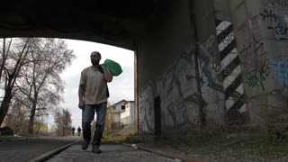 Front view full length of mature bearded unemployed man walking under bridge tunnel in city. Male holding plastic bin bags collecting plastic for recycling to survive. Steadicam stabilized shot.