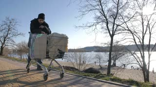 Front view of mature bearded homeless man walking on the road on a cold autumn pushing shopping cart with belongings. Full length unemployed beggar male walking in city. Steadicam stabilized shot.