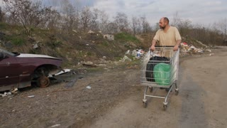 Front view of mature homeless man in dirty t-shirt walking at garbage dump site with abandoned old cars, pushing shopping cart with his belongings. Steadicam stabilized shot.