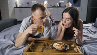 Front view of young cheerful happy couple lying in bed together in the morning, eating pancakes and drinking orange juice at home. Lovely man and woman chatting, eating and laughing together
