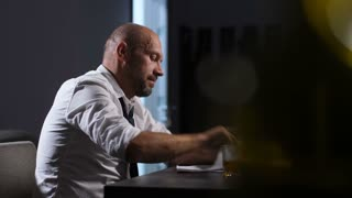 Frustrated adult businessman fed up hates, throwing documents and hitting table with fists in desperation after company bankruptcy while sitting at the desk with glass of whiskey in evening office.
