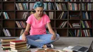 Frustrated student having a lot to read in library