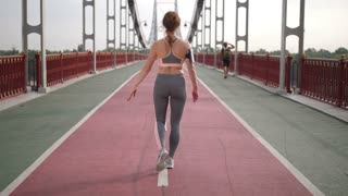 Full length back view of fit senior redhead woman with slim beautiful body stretching leg muscles and starts running forward on city bridge in the morning. Fitness lady working out in city before work
