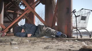 Full length cold homeless beggar male in jacket sleeping under the bridge in fall, eyes covered with hat. Urban homeless person with no home staying overnight outside. Dolly shot