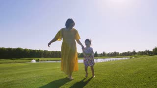 Full length mother and daughter holding hands and running together on green grass meadow in park during summer. Happy family barefoot running and enjoying while laughing and smiling out of delight